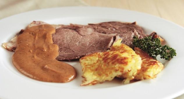 Lomo de ternera a la sal con salsa de ciruelas y naranjas y guarnición de rostí de patata.